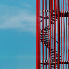 Close-up of red metal staircase against blue sky