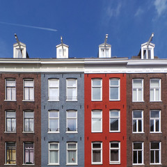 Four building facades in different colors in a row