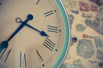 Vintage clock close-up on a stone wall background