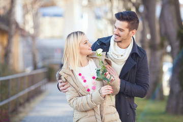 Outdoor portrait of an affectionate young couple with a rose