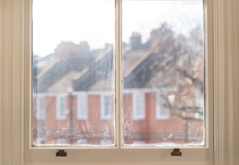 Old white window frame of victorian house with view of tenements