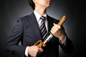 侍の刀を持っているスーツのビジネスマン