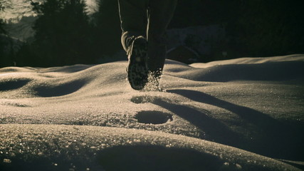 Woman walking on deep snow and cave, steadycam shot, slow motion