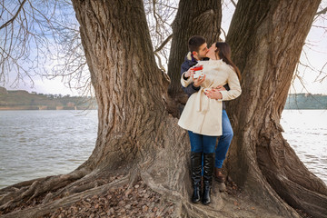 Romantic young couple holding gift and kissing in nature