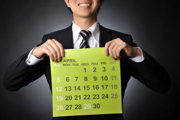 4月のカレンダーを持っているビジネスマン