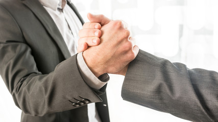 Conceptual Businessmen Gripping Their Hands
