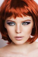 Красивая девушка с рыжими волосами на белом фоне.