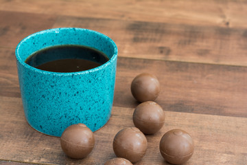 Teal coffee cup full of black coffee and chocolate