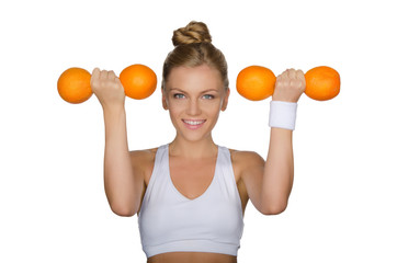 Beautiful woman with dumbbells of oranges