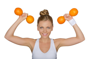 Beautiful woman with dumbbells from ripe oranges