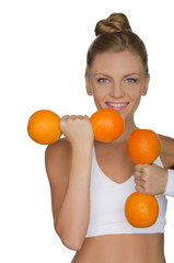 Beautiful girl with weights of ripe oranges