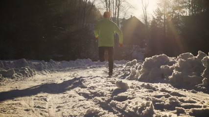 Man running at sunny day on snowy road, steady, slow motion
