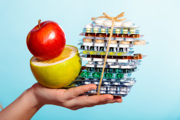 Human hand holding stack of pills and fruits on blue.