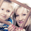 Portrait of mother and son holding photo frame
