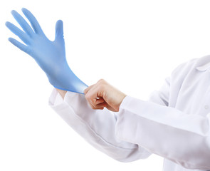 Doctor putting on sterile gloves isolated on white