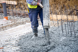 construction worker pouring cement or concrete with pump tube