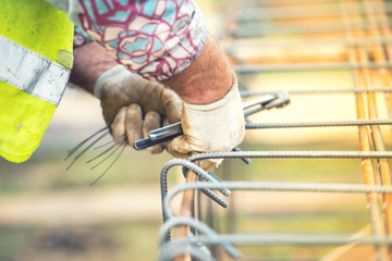 worker using steel wire and pincers to secure steel bars