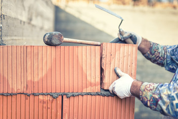 Construction bricklayer building walls with  bricks and mortar