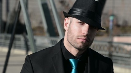 Tilt shot of a man in a suit and hat