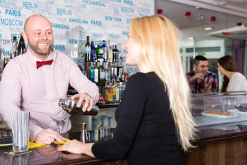 Smiling barman mixing cocktails