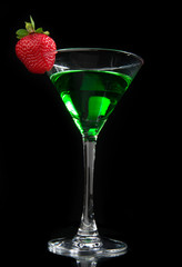 Green cocktail absinth decorated with red strawberry in martini