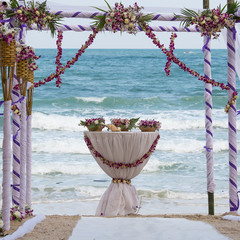wedding arch decorated with flowers on tropical sand beach