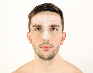 Handsome young man with cream lotion on face isolated on white