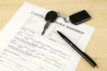 Car keys on insurance documents, close up