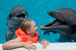 Happy Little Girl Laughing with two Dolphins in Swimming Pool