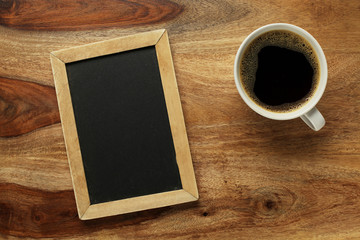 Cup of coffee on desk with blank chalkboard