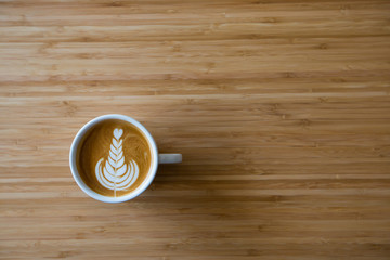 hot coffee latte serving on wooden table