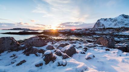 Snowy landscape on coast of Norway sunset