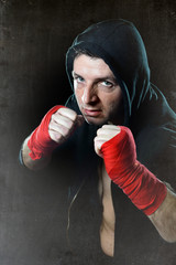 fighter man in boxing hood with wrapped hands in tough stance