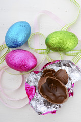 Chocolate Easter eggs on white vintage wood table.