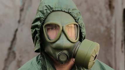 Portait of man with gas mask in protective clothing,watching