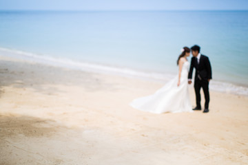 Out of focus of Bride and groom on tropical beach
