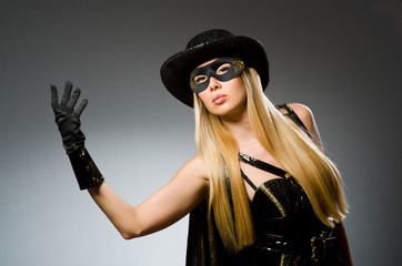 Woman wearing mask against dark background
