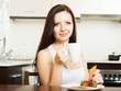 woman having breakfast at  kitchen