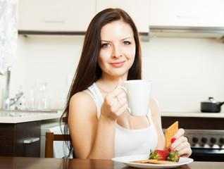 woman having breakfast at  kitchen