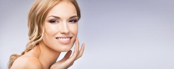 Woman touching skin or applying cream, on grey
