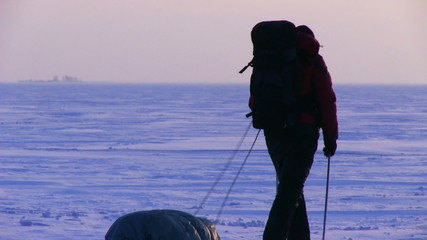 One man go to sunset on snow desert