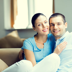 Cheerful smiling young attractive couple, indoors