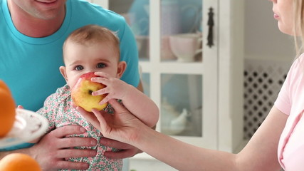 happy young family with baby eats in the kitchen - dolly shot