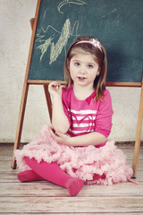 Little child sitting in front of the blackboard.