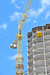 canvas print picture - Crane and building construction site against blue sky