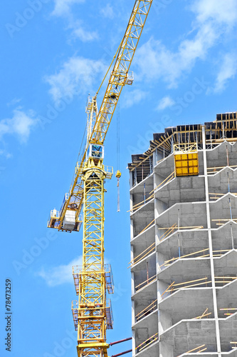 canvas print picture Crane and building construction site against blue sky