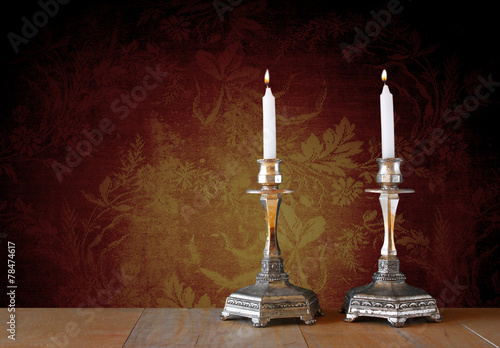 two candlesticks with burning candles over wooden table and vint - 78474617