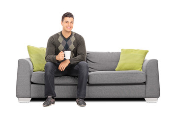 Man holding a cup of coffee seated on sofa