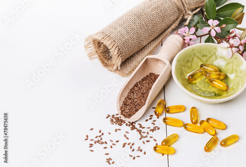 Leinwanddruck Bild Linseed and flaxseed oil capsules over white background