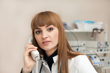 Beautiful female doctor talking on the phone